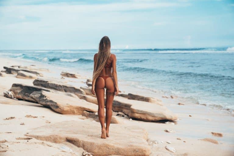 Ein hübsches Mädchen mit langen Haaren in einem schwarzen Bikini geht am Strand spazieren