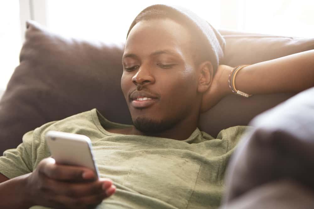 Ein junger schwarzer Mann liegt auf der Couch und benutzt ein Handy