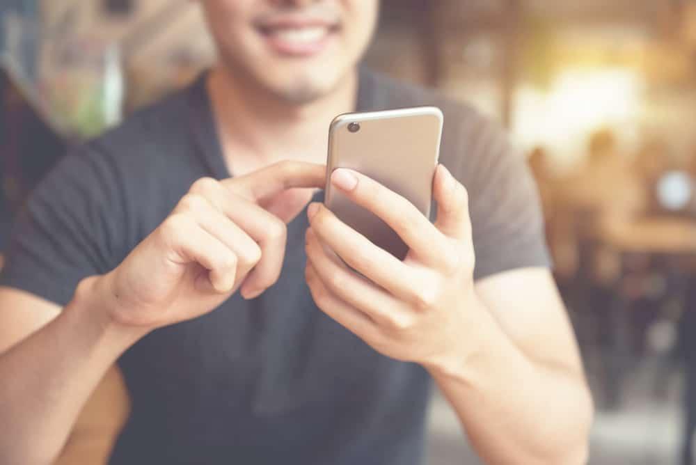 Ein lächelnder Mann benutzt ein Smartphone