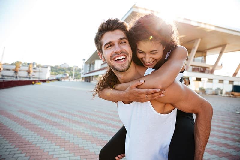 Ein lächelnder Mann trägt seine Frau auf dem Rücken