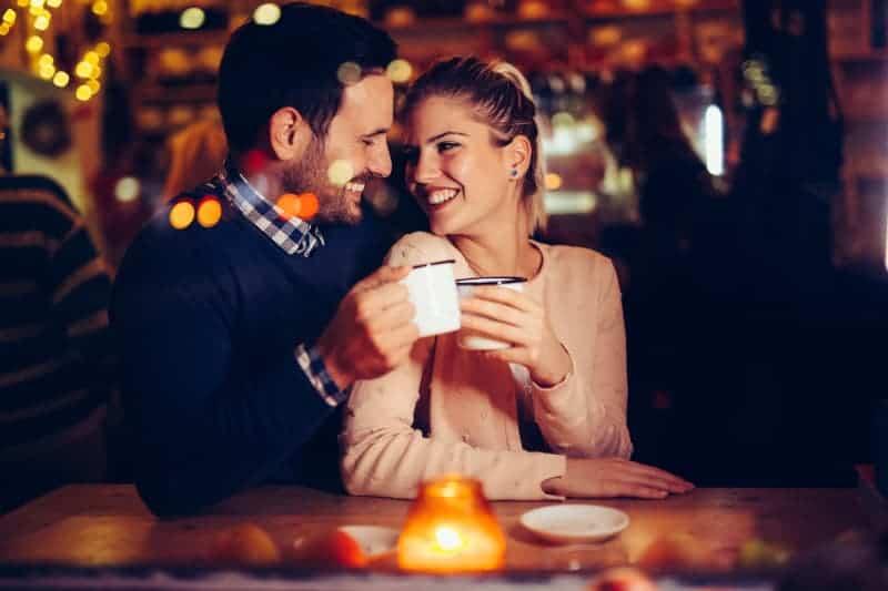 Ein lächelnder Mann und eine lächelnde Frau genießen ein heißes Getränk in einem Café