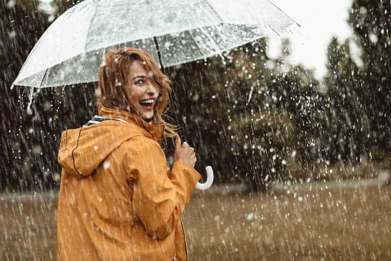 Ein lächelndes Mädchen mit einem durchsichtigen Regenschirm geht im Regen