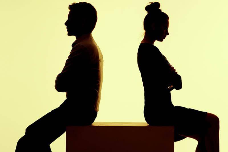 Ein streitsüchtiges Liebespaar sitzt mit dem Rücken zueinander