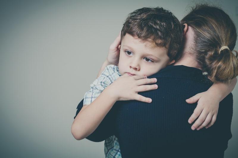 Ein trauriger Junge umarmt seine Mutter