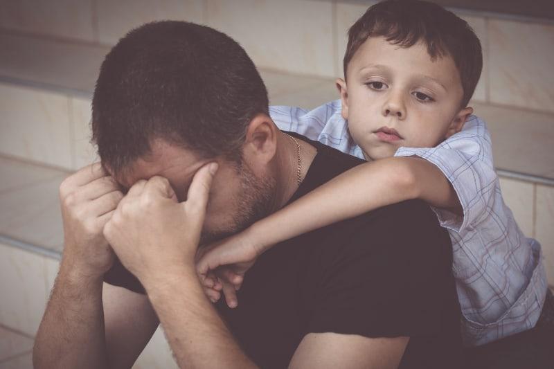 Ein trauriger Junge umarmt seinen desinteressierten Vater