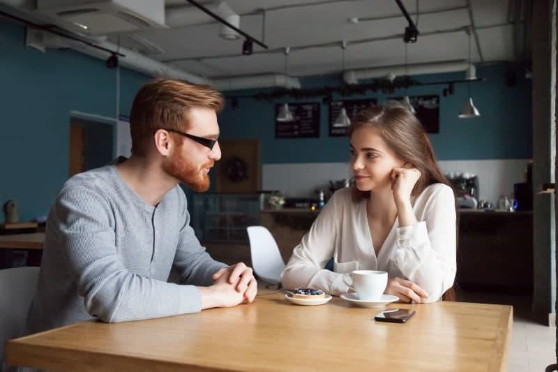 Eine Frau beobachtet ihren verliebten Mann, wie sie an einem Tisch in der Küche sitzt