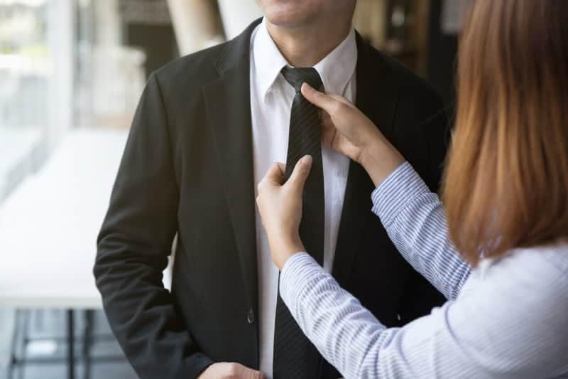 Eine Frau bindet eine Krawatte an ihren Mann