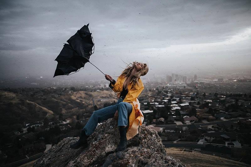Eine Frau in einem gelben Regenmantel mit einem kaputten Regenschirm genießt den Sturm