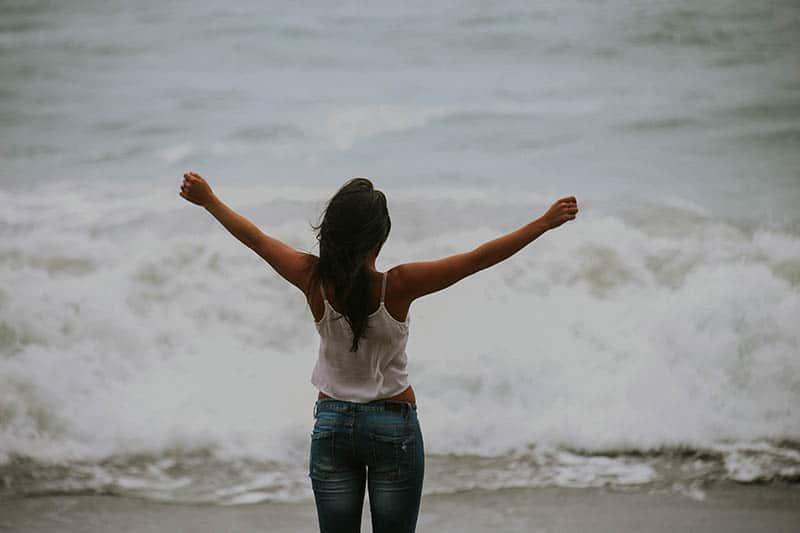 Eine Frau in einem weißen T-Shirt und Jeans steht mit ausgestreckten Armen am Meer