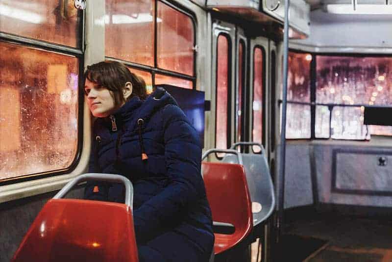 Eine Frau in einer Straßenbahn sitzt und schaut aus dem Fenster