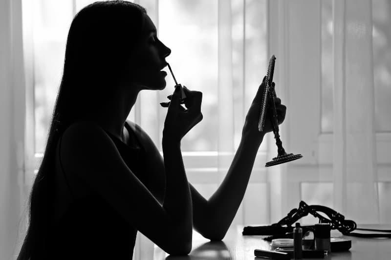 Eine Frau mit glattem Haar sitzt und schminken sich
