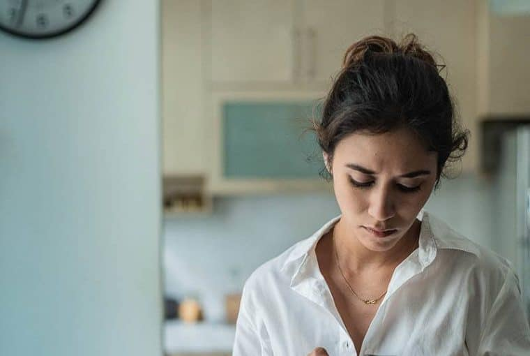 Eine besorgte Frau starrt auf den Küchenboden