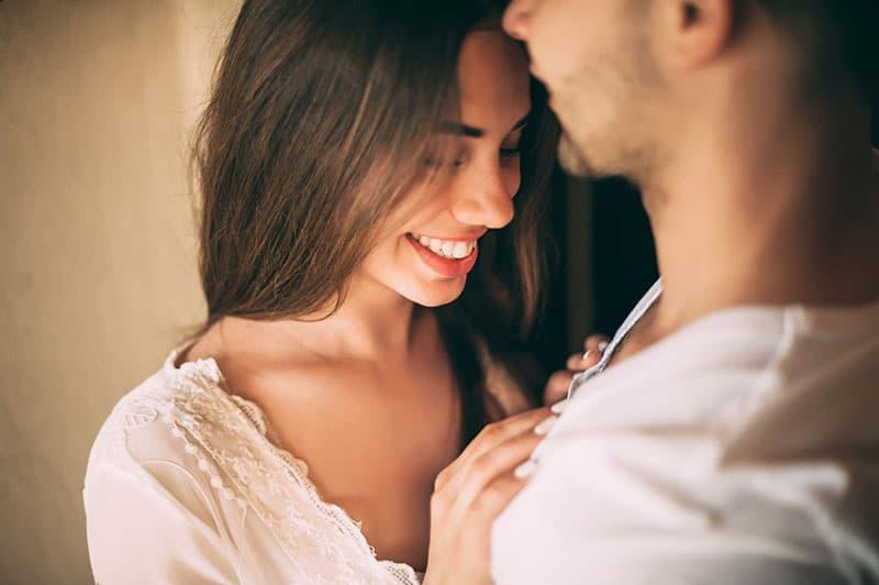 Eine lächelnde Frau hält ihre Hände auf der Brust eines Mannes
