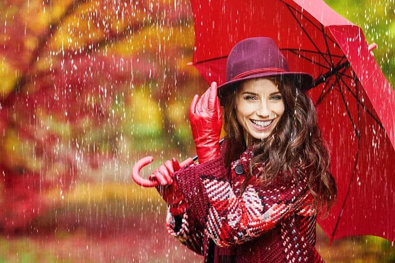 Eine lächelnde Frau mit roten Handschuhen und einem roten Regenschirm steht im Regen