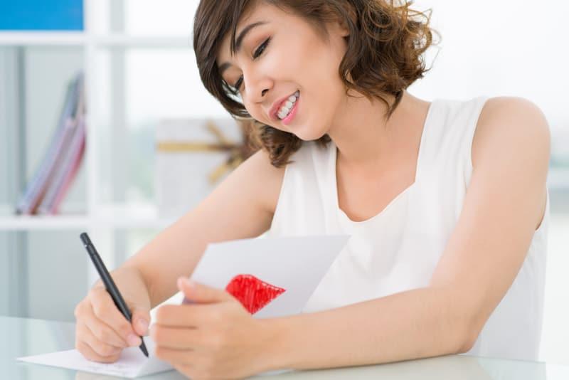 Eine lächelnde Frau schreibt eine Grußkarte