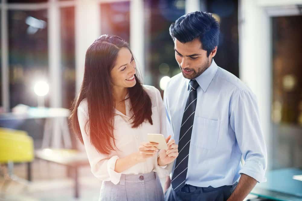 Eine lächelnde Frau zeigt einem gutaussehenden Mann etwas auf ihrem Handy
