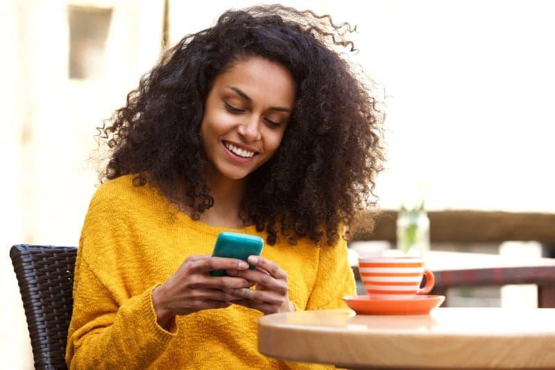 Eine lächelnde Mulattin mit krausem Haar sitzt und schreibt mit einem Lächeln eine SMS