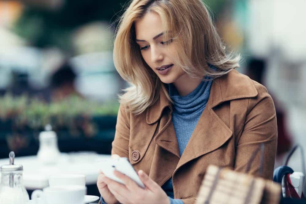Eine schöne Blondine in einem braunen Mantel sitzt auf der Terrasse eines Cafés und schreibt eine SMS