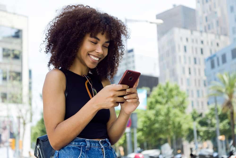 Eine schöne junge schwarze Frau mit einem Lächeln benutzt ein Handy