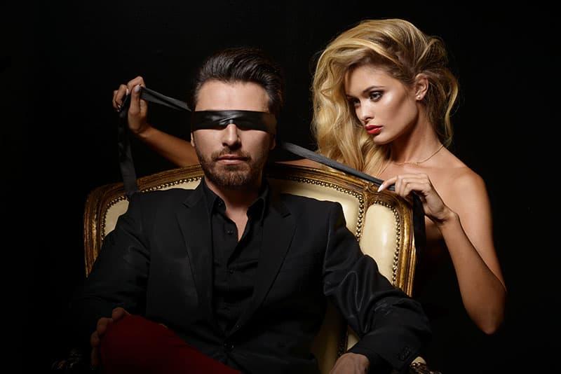 Eine sexy Frau mit einem Verband bedeckte die Augen des Mannes
