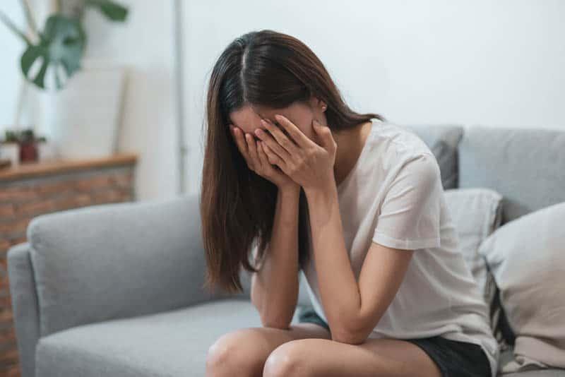 Eine traurige Frau sitzt auf der Couch und hält ihr Gesicht mit den Händen fest