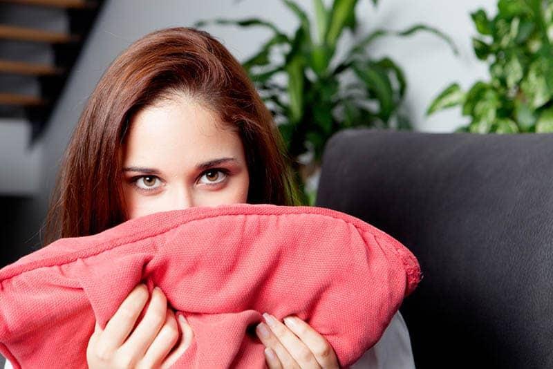 Frau mit braunen Augen, die Kissen halten