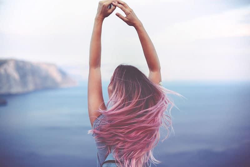 Frau mit rosa Haaren im Freien stehend
