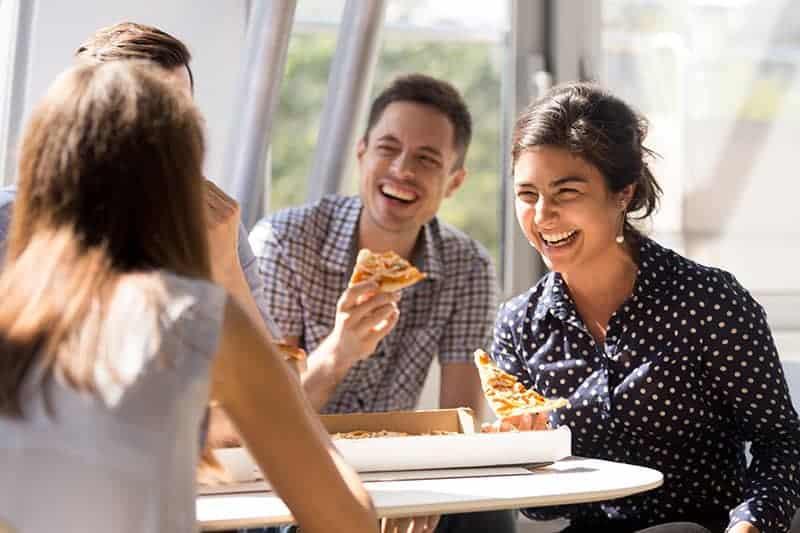 Gruppe von Freunden lachen und eine Pizza essen