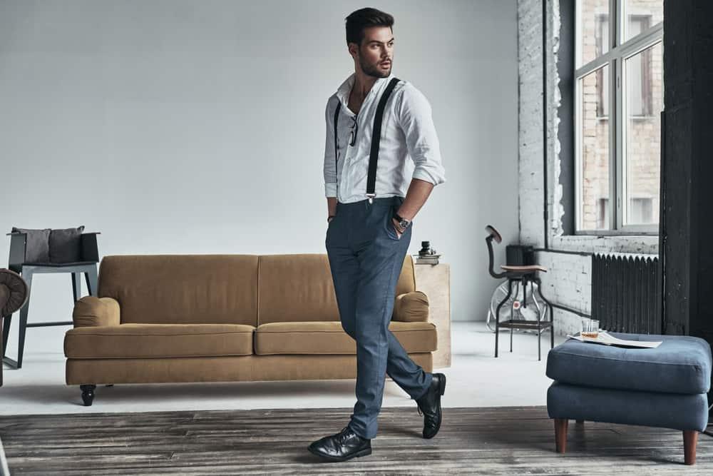 In der Wohnung steht ein gutaussehender Mann mit attraktiver Kleidung