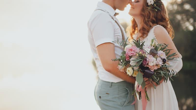 Jungvermählten in einer Umarmung mit einem Blumenstrauß