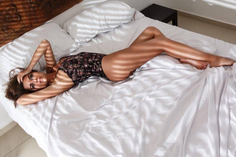 Mädchen in schwarzen sexy Dessous auf dem Bett