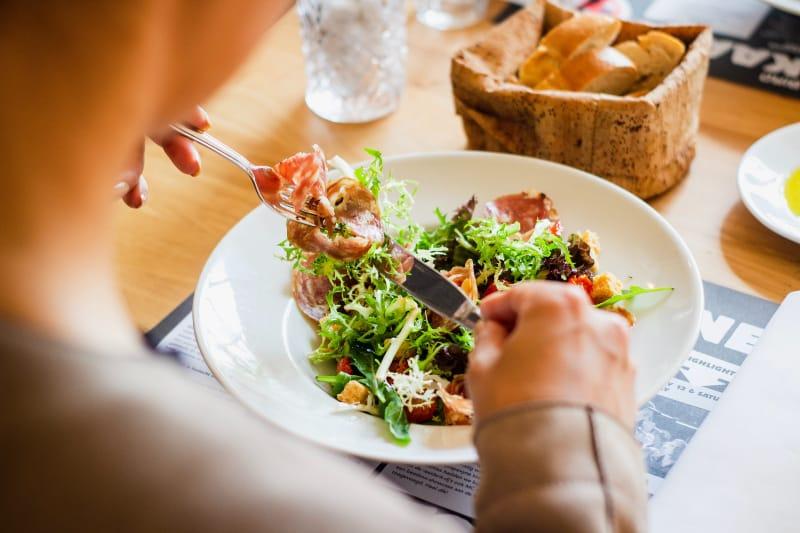 Mann, der Essen am Tisch isst