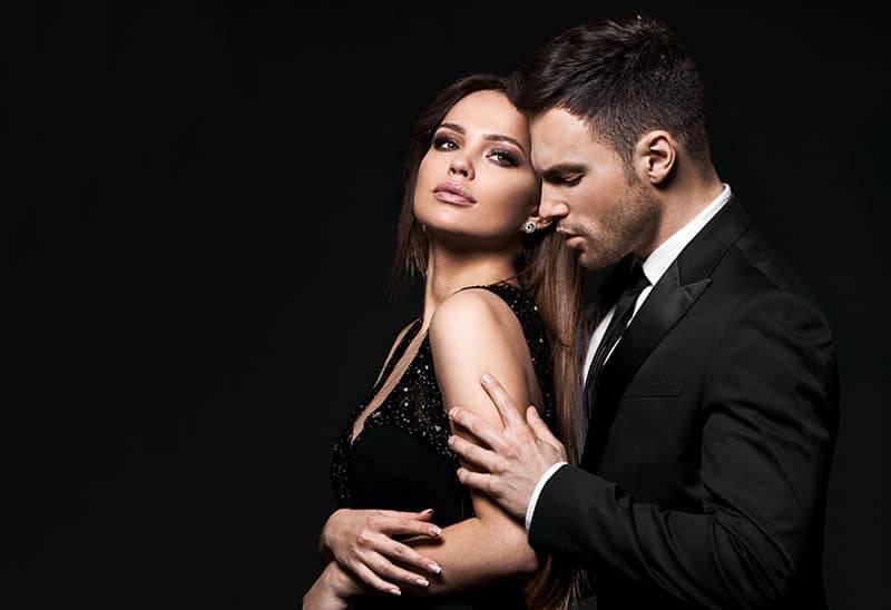Mann im schwarzen Anzug umarmt Frau im schwarzen Kleid