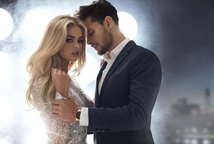 Mann im schwarzen Anzug umarmt Frau im weißen Kleid