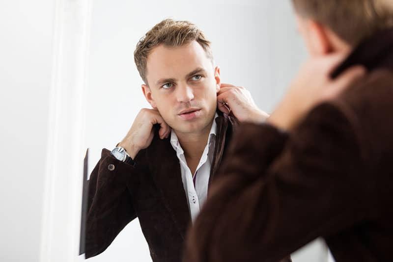 ernsthafter stilvoller Mann, der Spiegel betrachtet