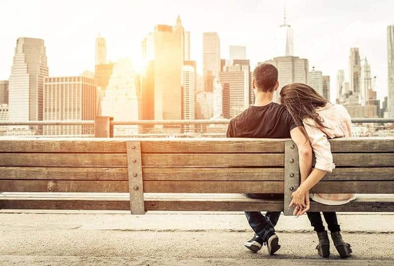 Paar Händchenhalten beim Sitzen auf Parkbank