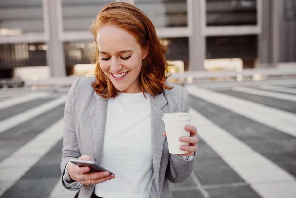 Porträt einer lächelnden Geschäftsfrau mit einem Telefon und Kaffee in ihren Händen