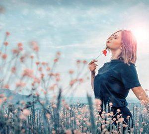 Eine zufriedene Frau steht allein auf einem Blumenfeld