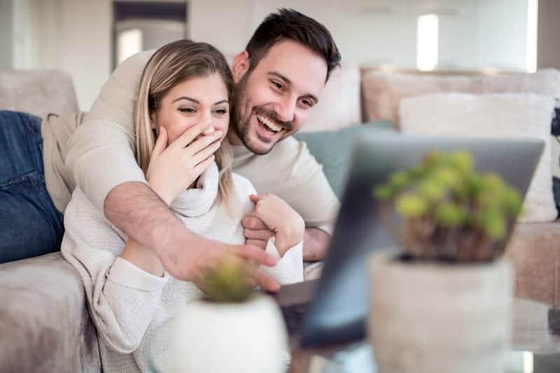 ein glückliches Liebespaar, das in einer Umarmung sitzt und etwas auf einem Laptop beobachtet