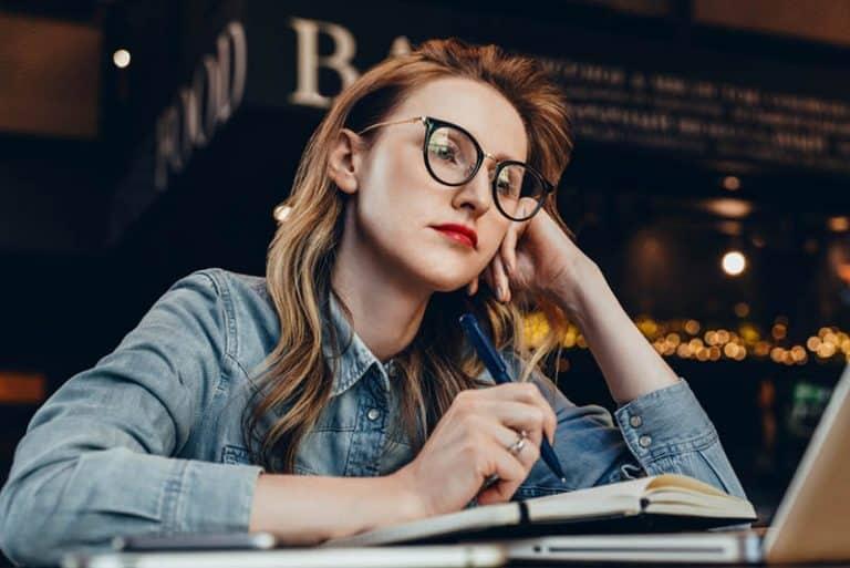 Ein besorgtes Mädchen schreibt in ein Notizbuch