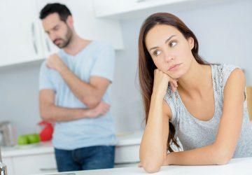 besorgte Frau, die auf dem Stuhl sitzt, während Mann steht
