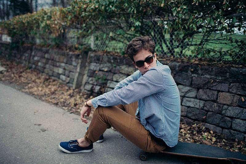 Mann, der blaues Hemd und schwarze Brillen sitzt auf Betonoberfläche sitzt