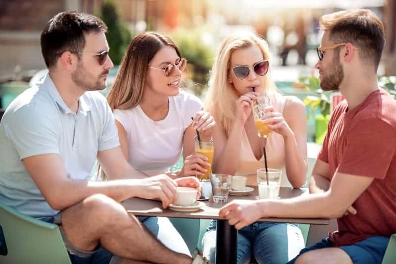 Zwei liebevolle Paare sitzen auf der Terrasse eines Cafés, nehmen ein Sonnenbad und trinken ihre Getränke