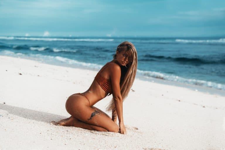 attraktive Blondine posiert am Strand in sexy Posen