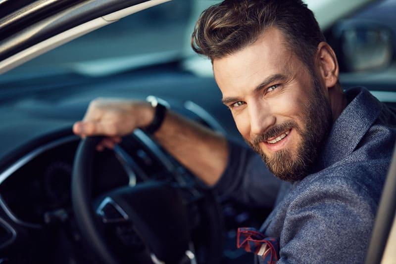 attraktiver Mann, der im Auto aufwirft