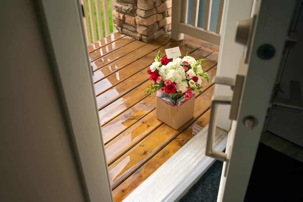 ein Blumenstrauß mit einer Liebesbotschaft vor der Tür