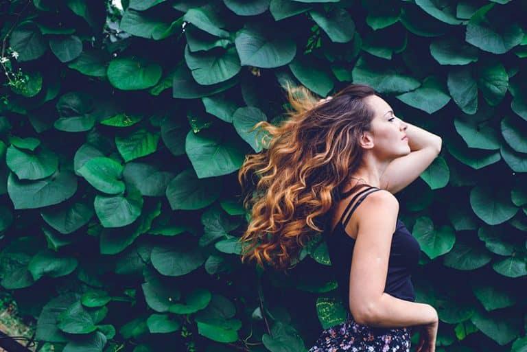 ein Mädchen posiert vor dem Grün