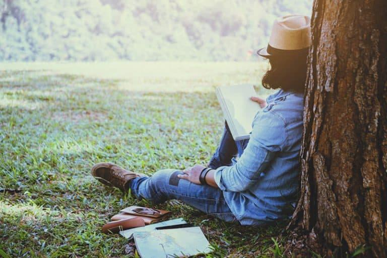 ein Mann, der ein Buch an einem Baum liest