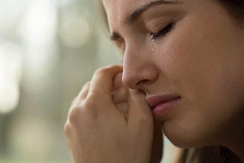 ein Porträt einer Frau mit geballten Fäusten, die weint