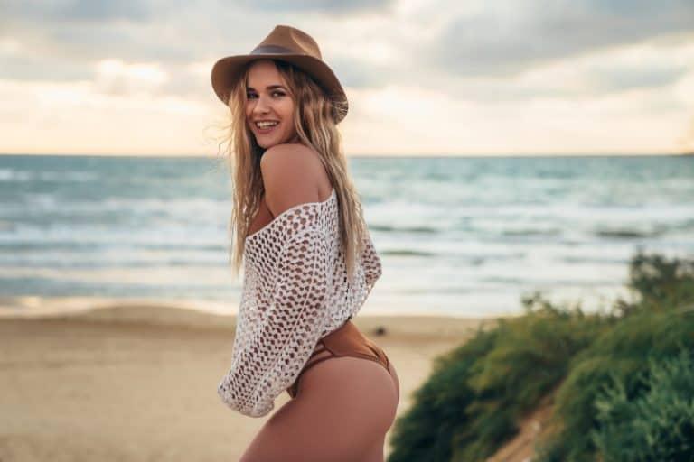 ein hübsches Mädchen mit einem Hut auf dem Kopf posiert am Strand